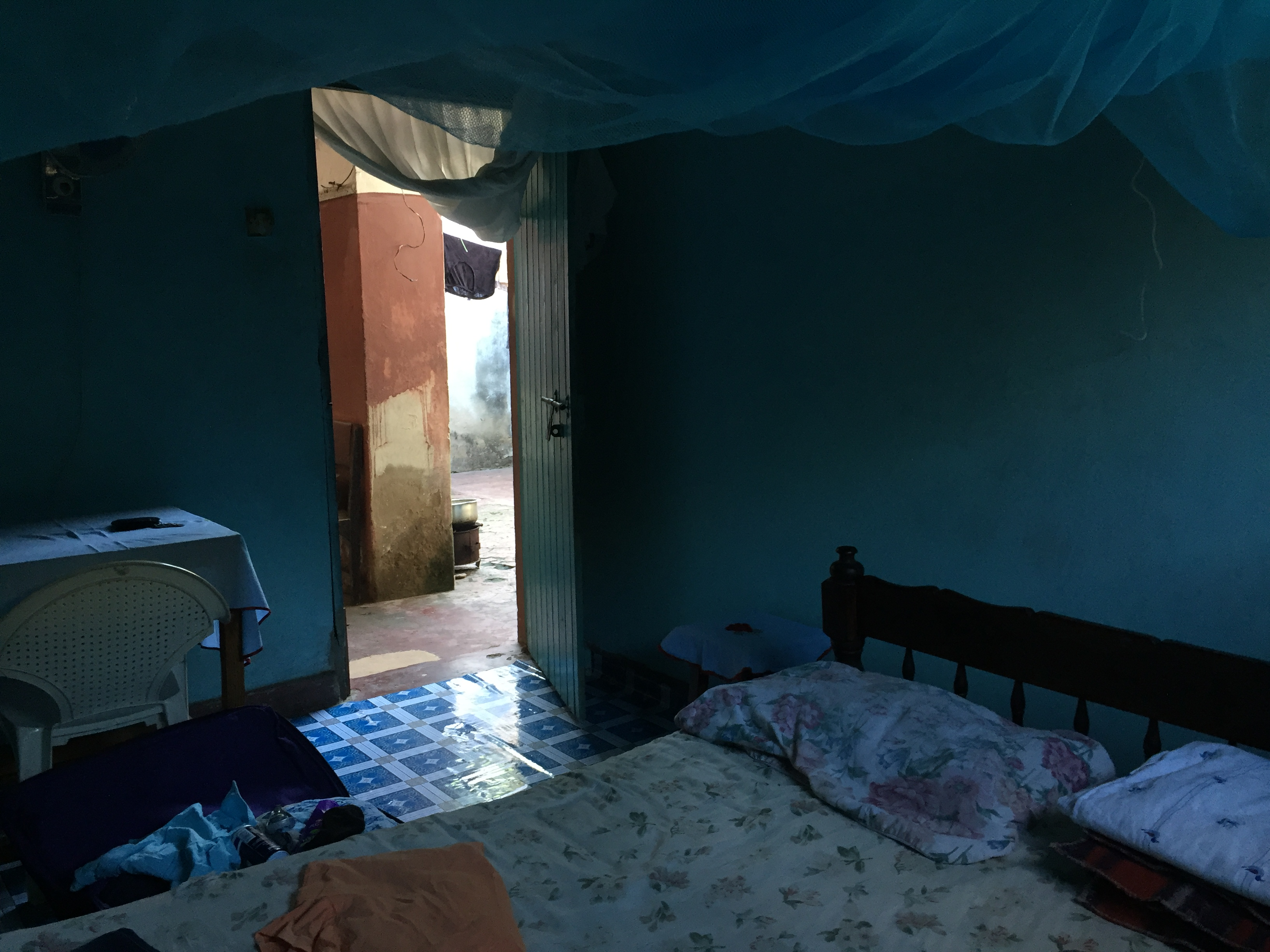 Dimly lit bedroom painted blue, showing bed with mosquito net hanging overtop and an open doorway to red concrete patio