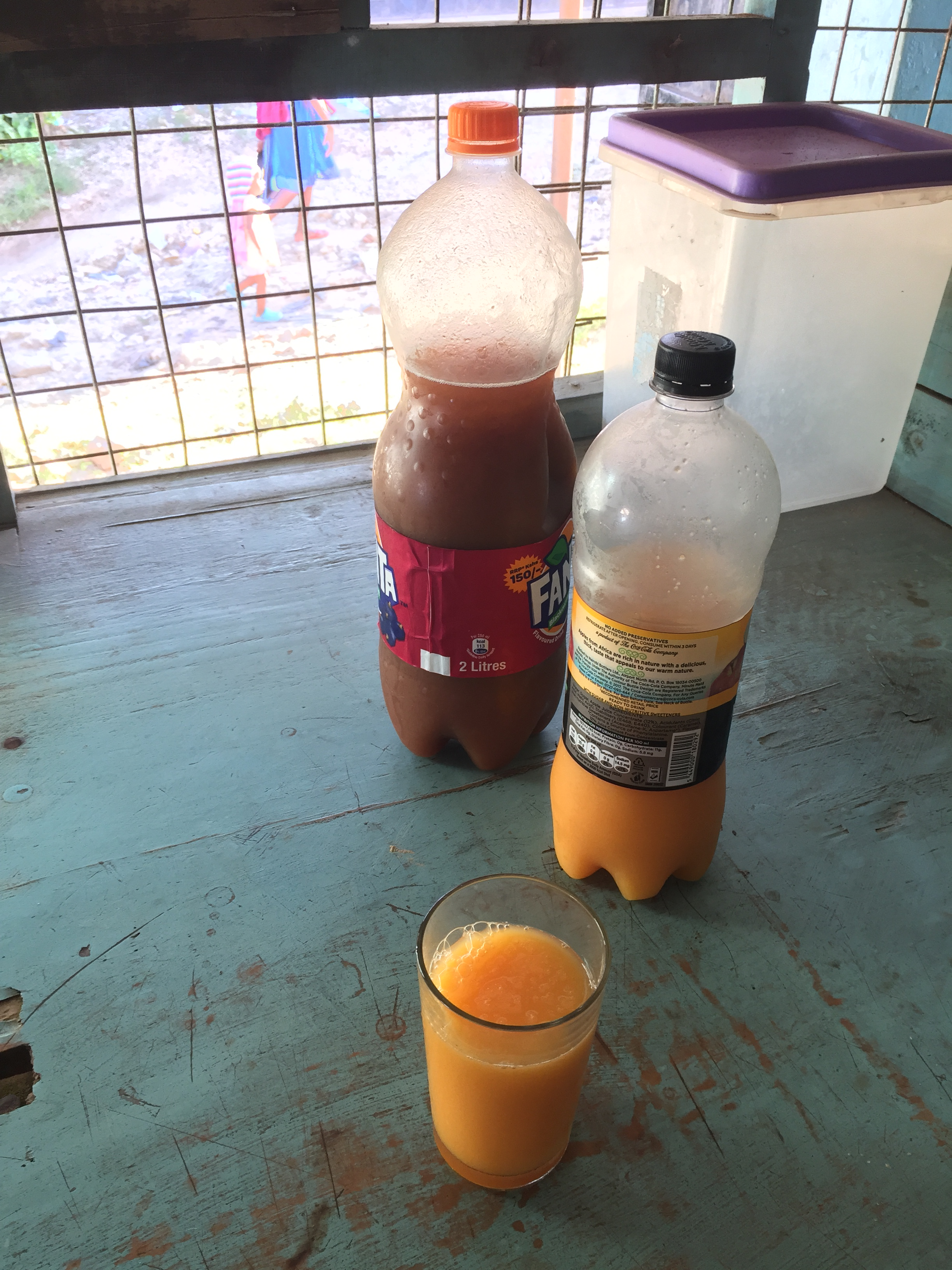 Two plastic bottles, one filled with tamarind juice and the other passionfruit, with a glass in foreground filled with passionfruit juice