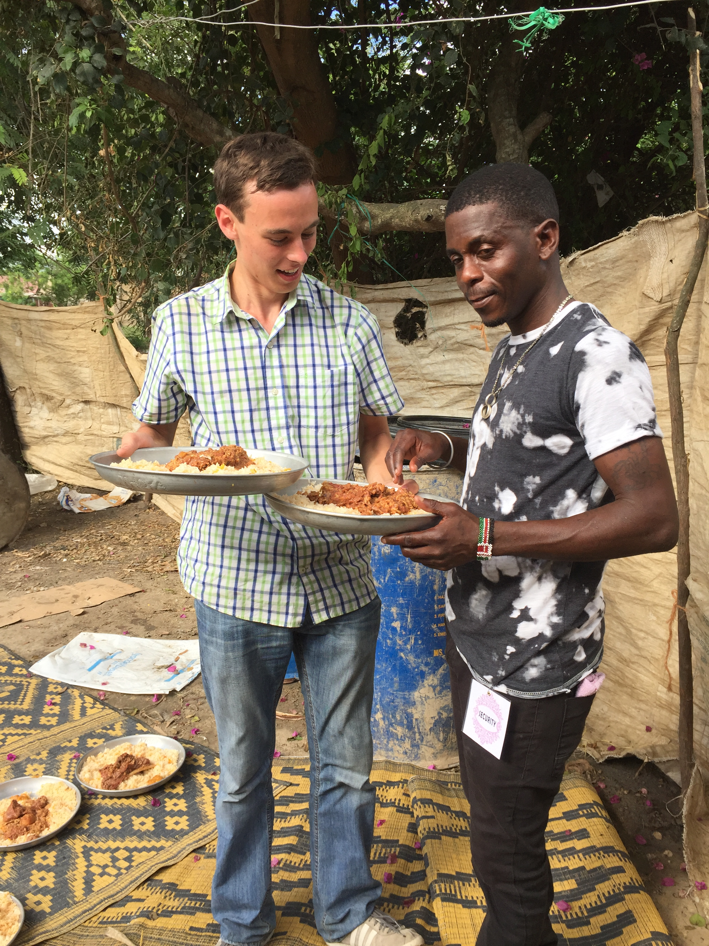 Dan holds two plates of biryani while another person feigns eating some